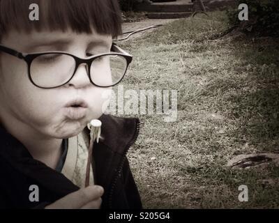 Make a wish (boy blowing a dandelion) - Stock Photo
