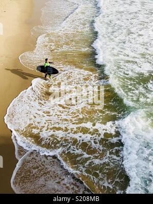 A male surfer walks out into the surf. Manhattan Beach, California USA. - Stock Photo