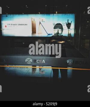 Silhouette of a walking person inside a shade of another person reflecting in a window and showing I Love You sign in silent language at a airport terminal with huge add lit up. - Stock Photo