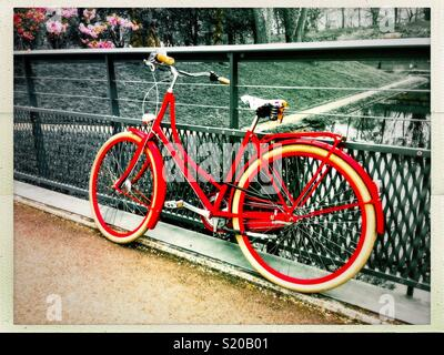 Beautiful vintage urban red bike on a bridge in a park. - Stock Photo