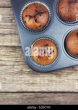 Top view of Chocolate muffins on a wooden table - Stock Photo