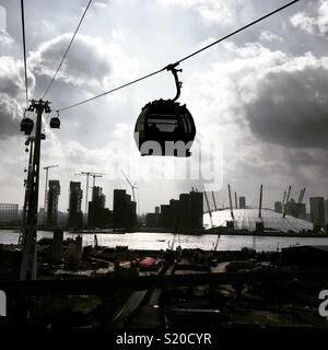 Emirates Air Line cable car moving above London. In the background is The O2. April 2018, London, United Kingdom - Stock Photo