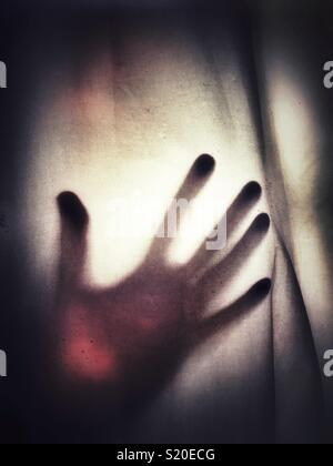 A silhouette of an outstretched hand against a see through fabric - Stock Photo