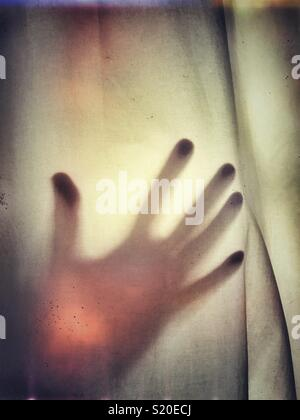 An outstretched hand against fabric - Stock Photo