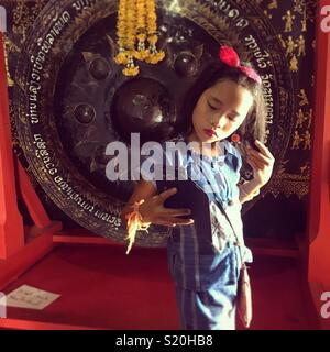 Laotian girl taking a selfie photo of herself in a temple in Luang Prabang - Stock Photo