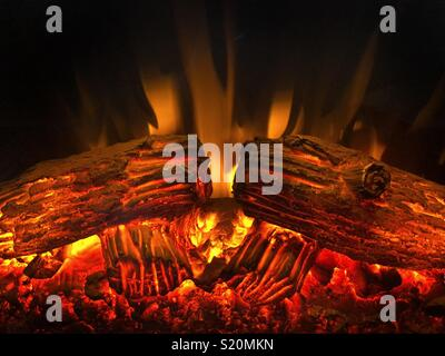 Red hot flames and burning logs in a faux fireplace Heater - Stock Photo