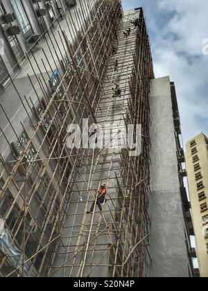 Workmen form a human chain to dismantle bamboo scaffolding after renovations on a highrise residential building in Wan Chai, Hong Kong Island - Stock Photo
