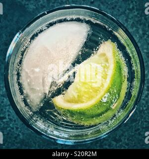 Top view of single ice cube and lime wedge in a glass of sparkling water