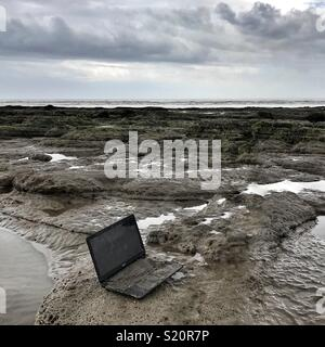 Laptop discarded on the beach - Stock Photo