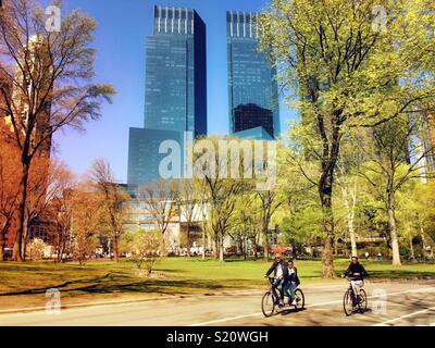 Bicyclist ride on the West Drive in Central Park with Columbus Circle buildings in the background, NYC, USA - Stock Photo