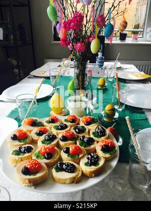 Easter decorated table with kids/ fun ladybird sandwiches with Easter egg candles and colourful decorations - Stock Photo