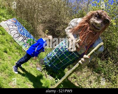 Boy by troll in the countryside - Stock Photo
