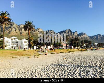 White sandy beach of Camps Bay in Cape Town with the 10 Apostles mountains in the background - Stock Photo