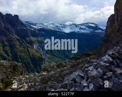 Snow capped mountains in Spring with rocky landscape below in the French Alps - Stock Photo