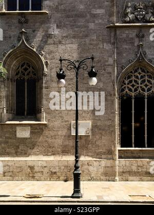 Street lamp in front of the facade of La lonja in Valencia - Stock Photo