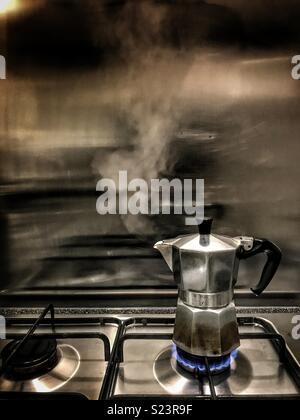 Coffee pot bubbling on the stove - Stock Photo