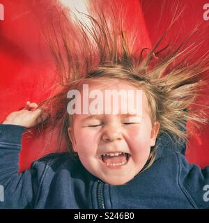 Portrait of happy toddler girl face as she slides down a red slide with eyes closed, mouth open and hair sticking up from static electricity - Stock Photo