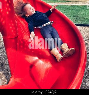Toddler girl smiling happily while sliding down a red playground slide - Stock Photo