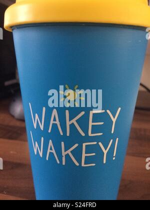 Hot drink travel cup, bright blue with a yellow top and wakey wakey written on the front - Stock Photo