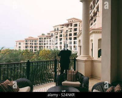 A man looks out from the balcony of a hotel in Abu Dhabi - Stock Photo