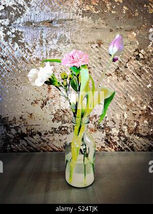 Cut flowered in glass bottle - Stock Photo