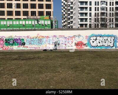 Graffiti artist doing work on the Berlin Wall near to the East side gallery.