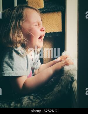 Toddler girl crying at a window during a temper tantrum - Stock Photo