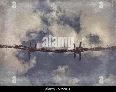 Barbed wire seen through dirty window with raindrops - Stock Photo