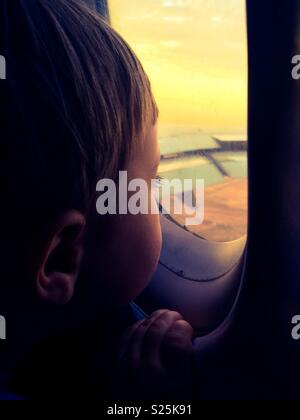 Toddler boy looking out airplane window at sunset while in flight, Haze filter applied - Stock Photo