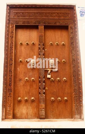 Ornate carved wooden Swahili door in Lamu, Kenya - Stock Photo