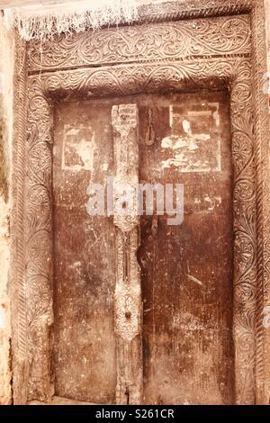 Old, damaged, Swahili wooden carved door in Lamu, Kenya - Stock Photo