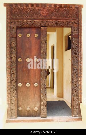 Ornate Swahili carved wooden door in Lamu, Kenya - Stock Photo