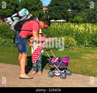 Father helps his daughter with her baby doll. - Stock Photo