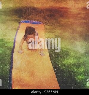 Little girl playing on a slip and slide - Stock Photo