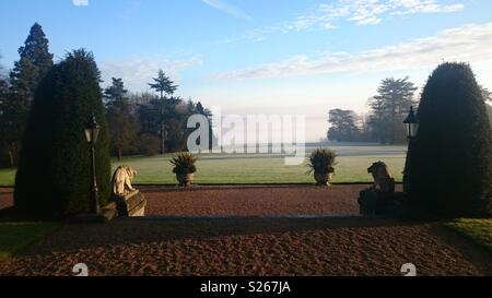 View down the lawn at the back of The Mansion House at the Luton Hoo Hotel, towards the River Lea. Early morning mist obscures the view of the water. Shot from the Wernher Restaurant in Winter. - Stock Photo