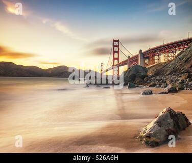 Golden sunset light on the Golden Gate Bridge from Marshall's beach in San Francisco - Stock Photo