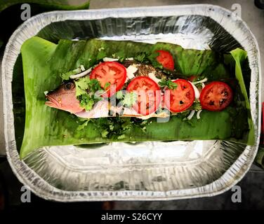 A red snapper baked on banana leafs with tomatoes, onion and coriander in Todos Santos, Baja California, Mexico - Stock Photo