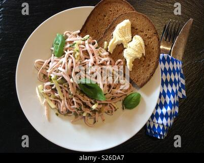 Bavarian sausage and cheese salad and  farmer's bread on white plate on beer garden, Bavaria, Germany, Europe - Stock Photo