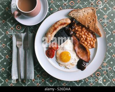 Overhead view of a homemade full English breakfast, with sausage, tomatoes, black pudding, mushrooms, baked beans, toast, brown sauce, a fried egg, and a cup of tea. - Stock Photo