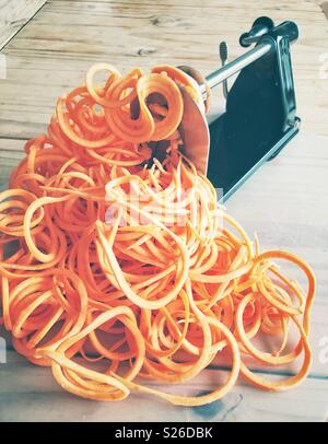 Heap of spiralized sweet potatoes in the process of being spiralized into vegetable noodles - Stock Photo
