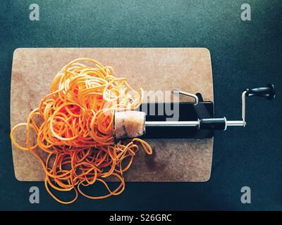 Flat lay view of sweet potato in the process of being spiralized - Stock Photo
