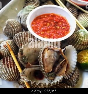 Clams and chilli sauce at East Coast Lagoon Food Village, a hawker food market in Singapore - Stock Photo