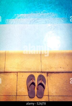 Entering swimming pool. Flat lay picture of a pair of flip-flops on the edge of a swimming pool. Summer concept. - Stock Photo