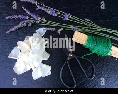 Elevated view on floristic background, blooming lavender, white rose, vintage  scissors and green florist wire - Stock Photo