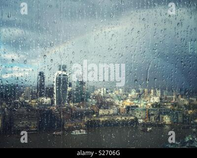 Rain on the window of The Shard, London, UK, looking across the Thames towards Fenchurch Street and over the City. A rainbow lights up the sky as the sun breaks through, lighting up the city below. - Stock Photo
