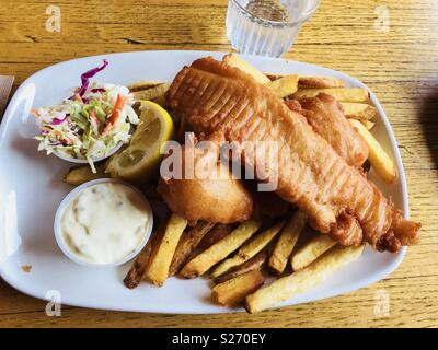 A plate of fish and chips with lemon wedge, tartar sauce and Cole slaw. - Stock Photo
