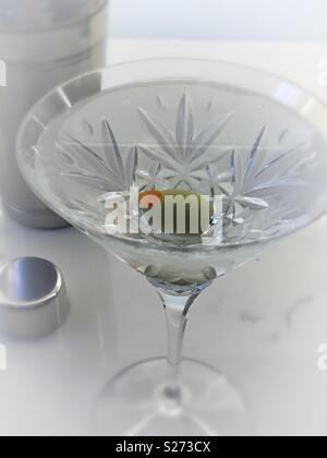 The classic dry gin martini next to a Cocktail shaker, served in a Waterford crystal martini glass, USA - Stock Photo
