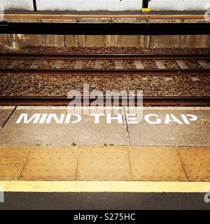 'Mind the gap' white painted sign on edge of railway platform - Stock Photo