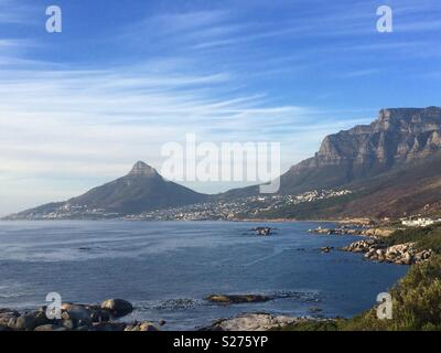 Landscape of Lions Head and back of Table Mountain across the sea and looking at Camps Bay an upmarket suburb of Cape Town - Stock Photo
