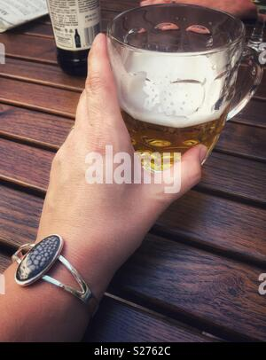 Woman holding a half drunk pint of beer in an old fashioned pint pot whilst sat by a wooden table. - Stock Photo